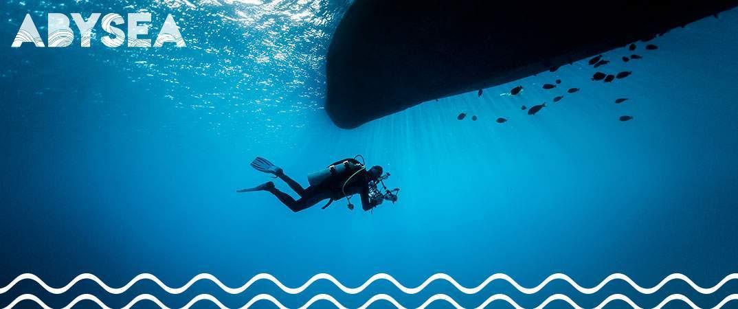 Plongeur naviguant sous la coque d'un bateau portant le pavillon alpha